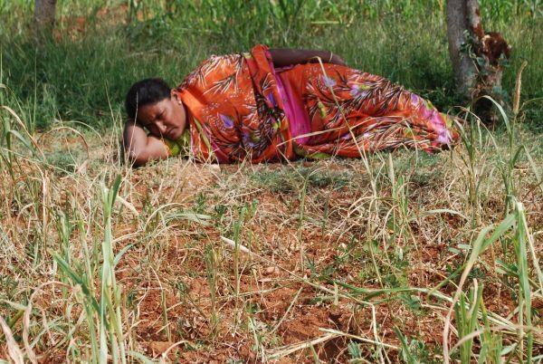 விவசாயம் கைக்கொடுக்காததால், விளைநிலத்தில் சோகத்தில் படுத்திருக்கும் விவசாயக் குடும்பத் தலைவி சித்ரா