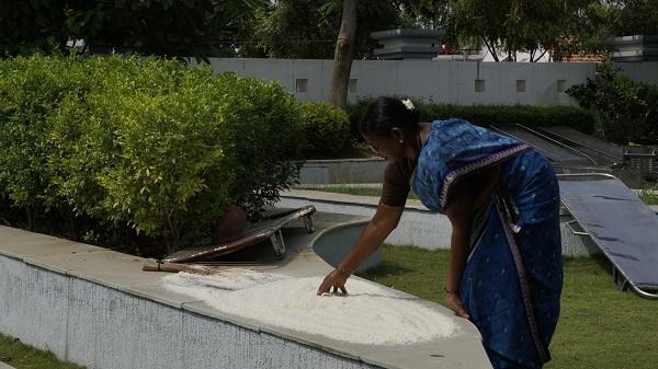 மயானத்தில் வாய்க்கரிசியை காயவைக்கும் பணிப்பெண்